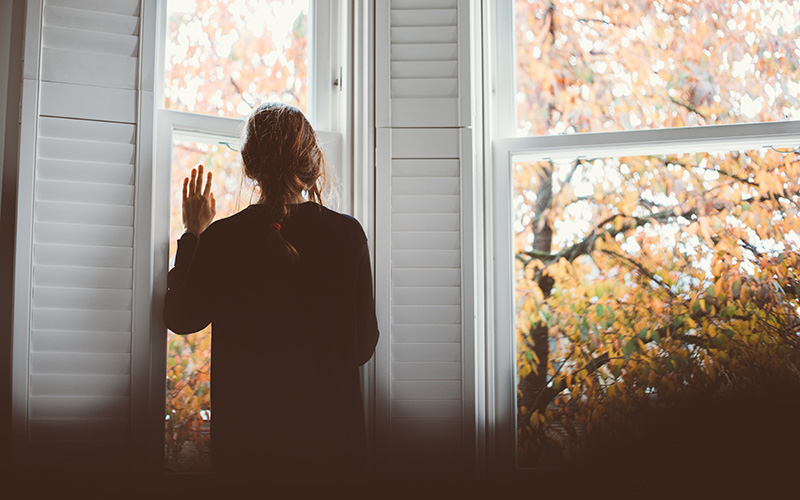 A long-haired person in a dark sweater seen from behind, leaning and looking out of a window during a bout of autumn blues
